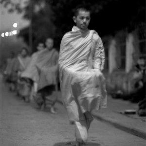 Buddhist monks walking dim street for alms