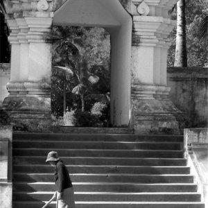 寺院の前を掃除する女性