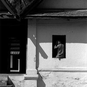窓辺に腰を下ろした若い僧侶