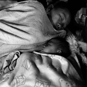 Mother and baby sleeping in night market