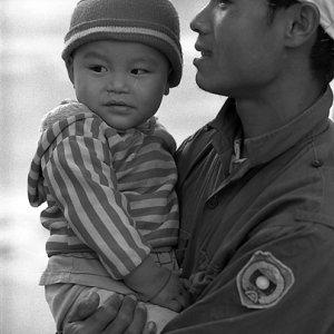 赤ちゃんを抱えながら歩くお父さん