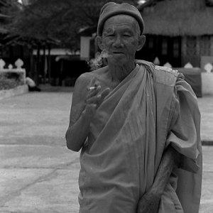 境内で煙草を吹かす年配の僧侶
