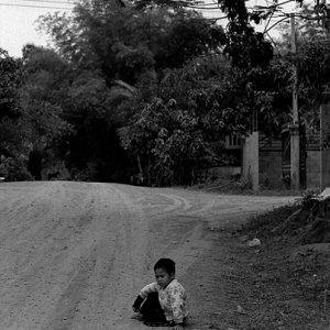 砂利道の脇に腰を下ろした男の子