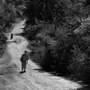 ひとりで砂利道を往く僧侶