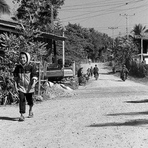 笑いながら砂利道を歩く男の子