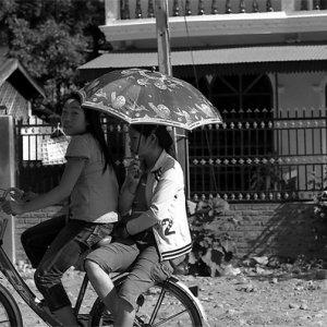 Two girl on same bicycle with sunshade