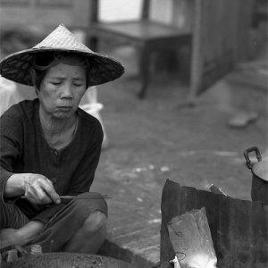 団子を揚げる女性