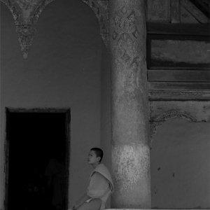 装飾の施された柱の横に腰を下ろした若い僧侶