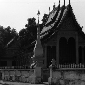 Buddhist monks walking beside a temple with umbrella