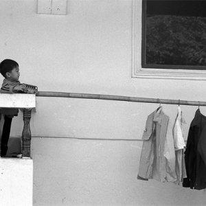 洗濯物のあるベランダで遊ぶ男の子