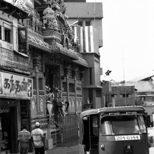 ヒンドゥー教寺院の前を通り過ぎるスリーウィーラー