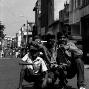 Three boys crouching down in the center of street