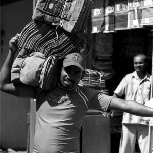 Man carrying textile on shoulder