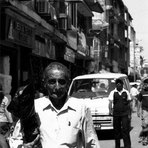 長い包を抱えて歩く男