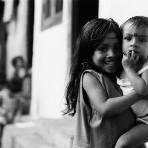 笑う赤子を抱えた幼い女の子