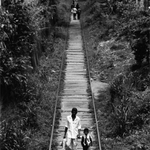 Father and son walking on railway track together
