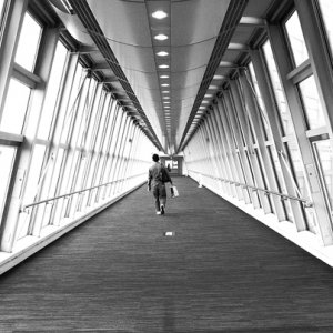 Man walking glass-made corridor