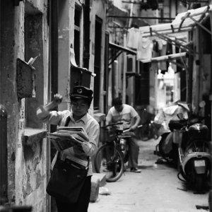 路地で配達する郵便配達の女性