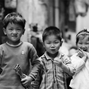 Two boys and one girl playing together in lane