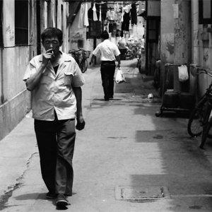 くわえ煙草で路地を歩く男