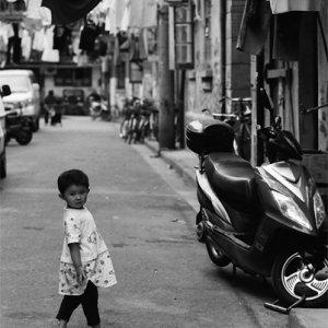 路地で振り返る幼い女の子