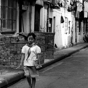 学校の制服を着て路地を歩く女の子