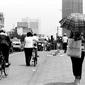 日傘を差して橋の上を歩く女性
