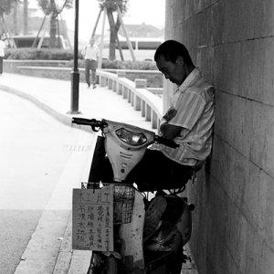 門の下の日陰で昼寝する男