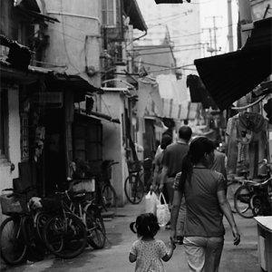 手をつないで路地を歩いていた若いお母さんと娘