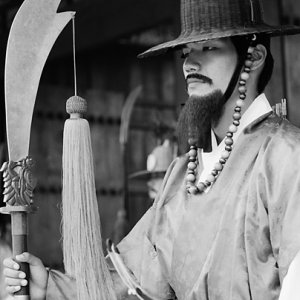 Man standing at gate with old costume