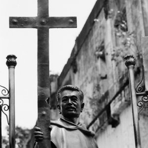 Statue of father holding a cross in its hand