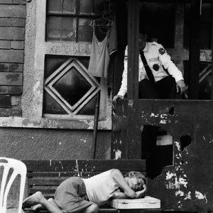 警備員の前にあるベンチで横になる女性