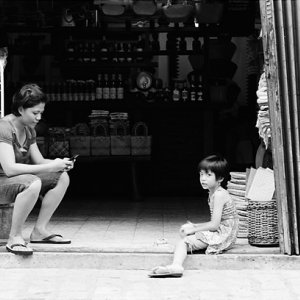 Woman and girl relaxing in storefront