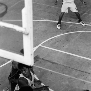 Young men playing basketball in gym