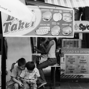 Boys playing hand-held game in front of food stall