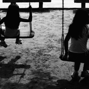Silhouetted girls playing on swing