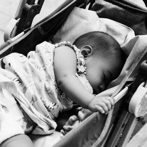 ベビーカーの中でぐっすり寝る赤ん坊