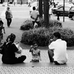 お父さんとお母さんの間に立つ幼い女の子