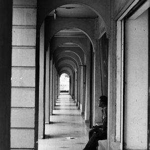 Man sitting alone in deserted passage