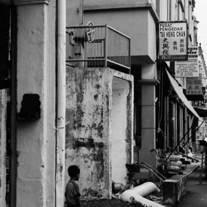 Boy standing still in twilight street