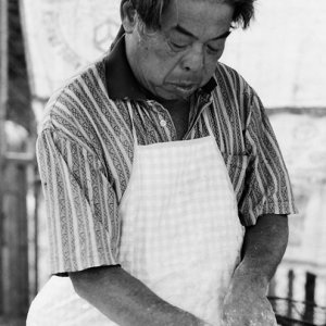 Man kneading dough in stall