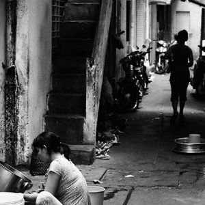 薄暗い路地で家事をする女