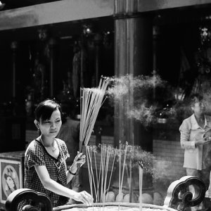 Woman sticking some long incense stick