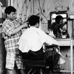 Barber cutting with serious face