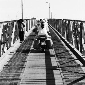 Many motorbikes crossing bridge