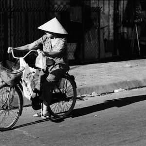 Women with conical hat riding bicycle