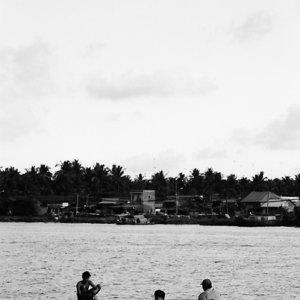 Three men on long and thin boat