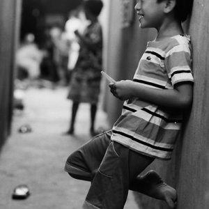 路地で独り笑いをする男の子