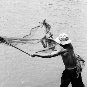 Man throwing fishnet in river