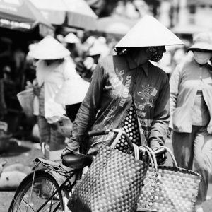 Woman walking bicycle in market